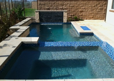 Pool and spa in Huntington Beach with infinity edge spa by Aquanetic Pools