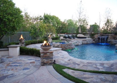Free Form Pool With Stone Pilasters & Fire Bowls