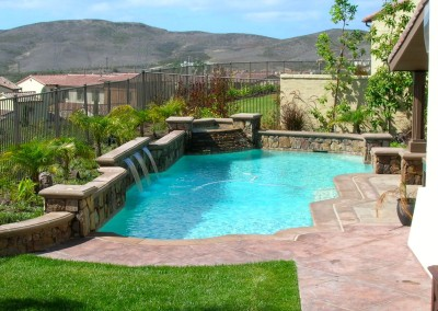Traditional Pool With Raised Planter Walls & Water Features